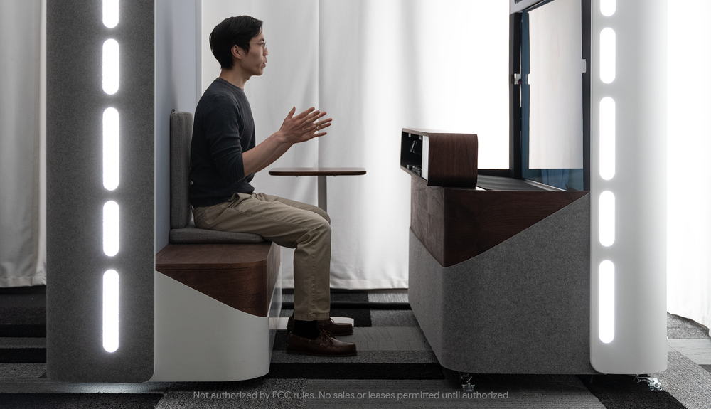 Image of a person having a conversation with someone in a booth using Project Starline.
