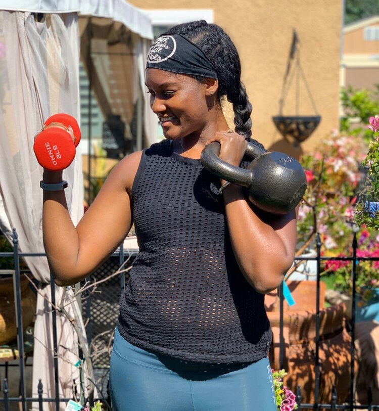 Brittany holds a hand weight and kettlebell wearing black top and blue pants