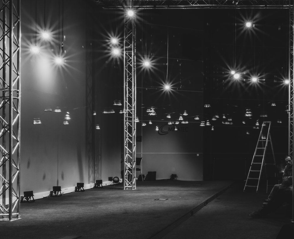 An empty stage with bells hanging on wires