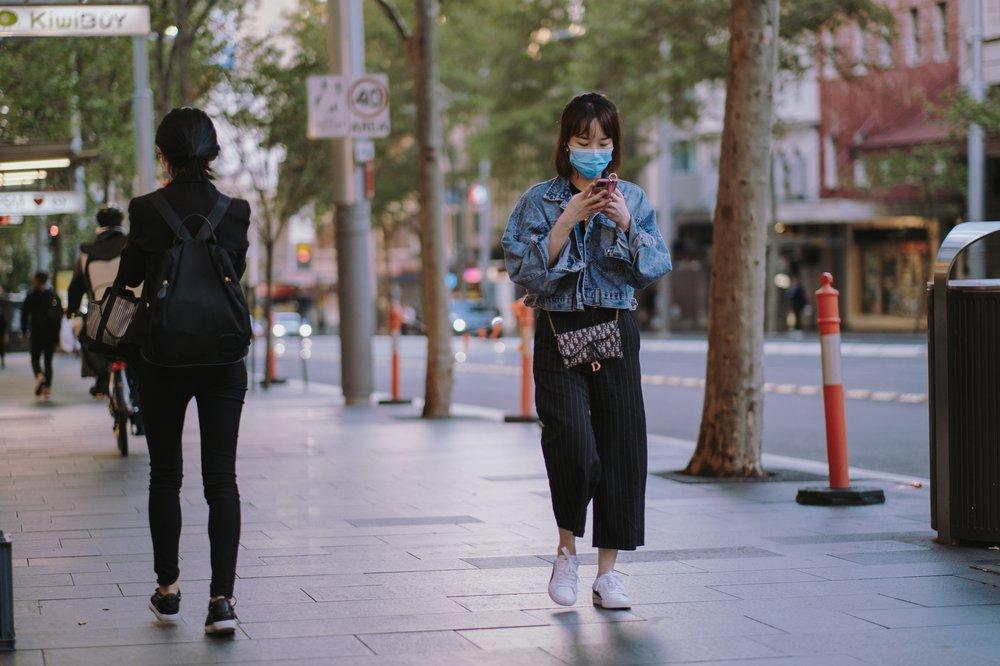 Frau mit Maske läuft auf einer Straße mit einem Smartphone in der Hand