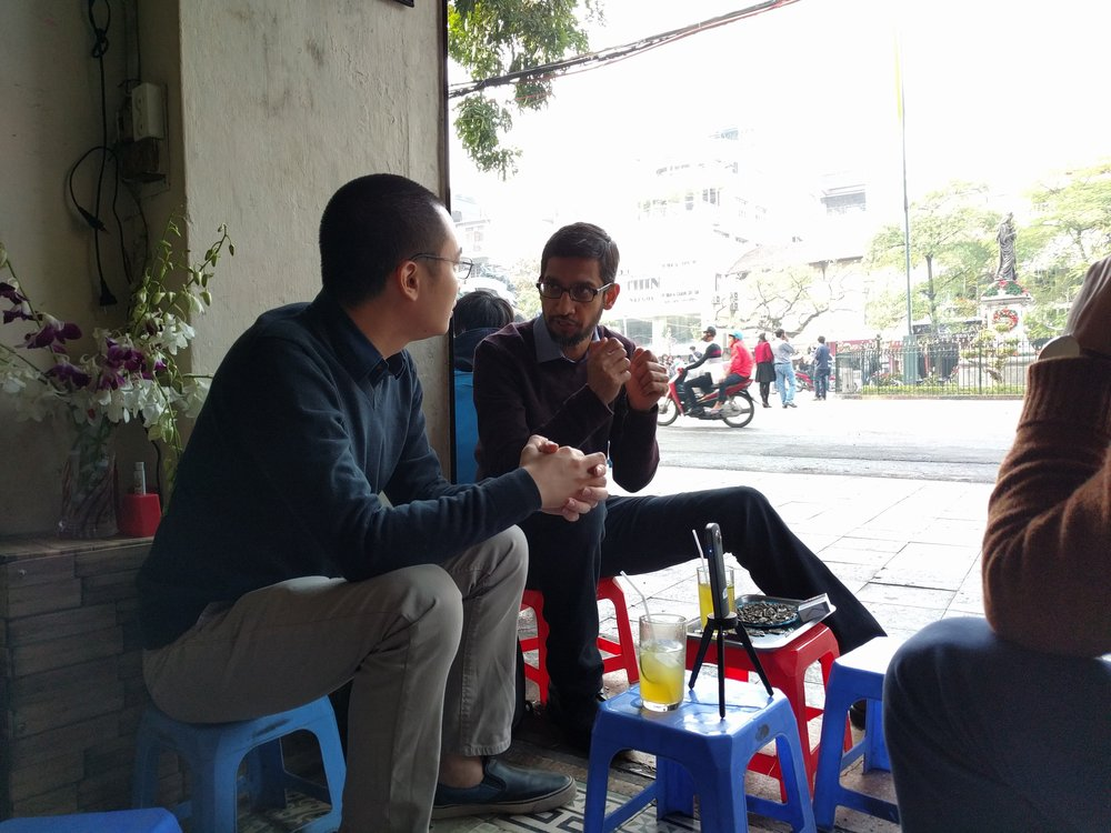 """Sundar Pichai in conversation with """"Flappy Bird"""" creator Dong Nguyen. They are sitting on low stools in a street-side cafe in Hanoi, with motorcycles, pedestrians, trees and shops in the background. A smartphone is propped on a stool in front of them."""