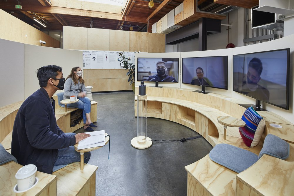 """A """"Campfire"""" space: A circular seating area with 2 people sitting in person, and 3 more on individual videoconference screens."""