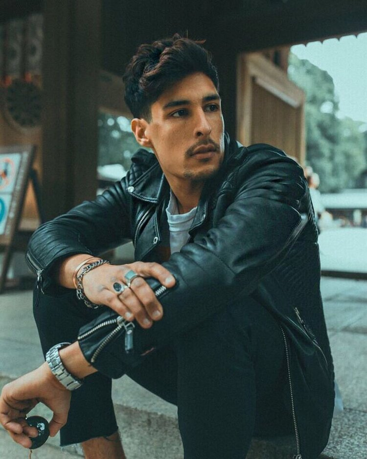 Carlos sits on the curb in style wearing a black leather biker jacket and black pants