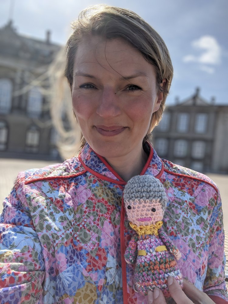 Christine poses with her crocheted Queen Margrethe II, the current queen of Denmark