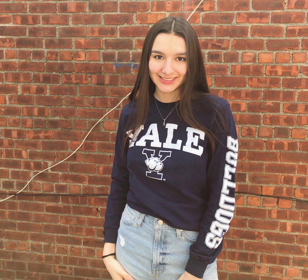 Cindy Hernandez wearing a Yale t-shirt standing in front of a brick wall