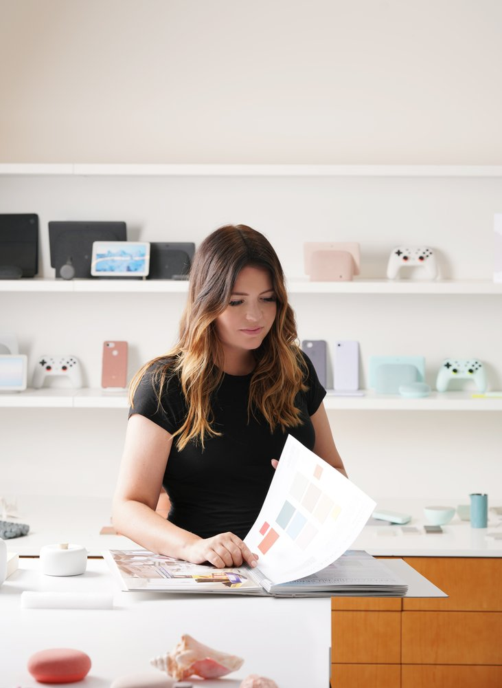 Isabelle Olsson stands at a desk in the Google CMF studio. White shelves behind her hold colorful inspiration objects in muted tones, pastels. She flips the pages of a large book.
