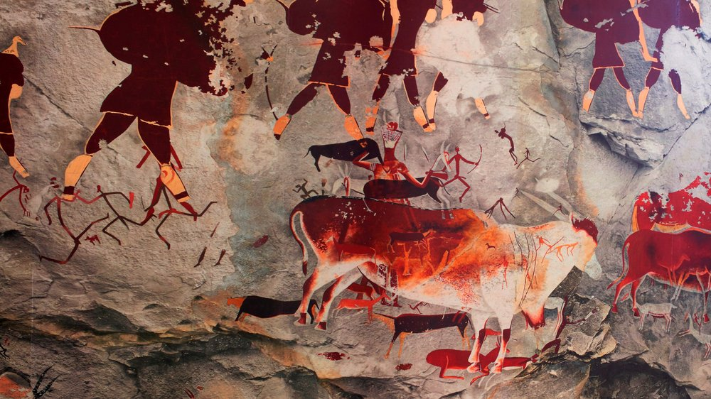 this image depicts painted images in shades of dark red, sand and brown and orange. The images show elands, half human and animal forms (known as therianthropes) and hunters holding bow and arrows.
