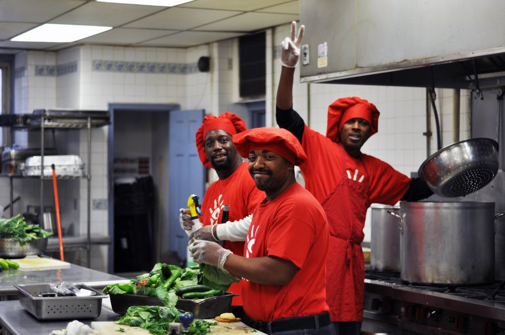 Three men working in a professional culinary kitchen
