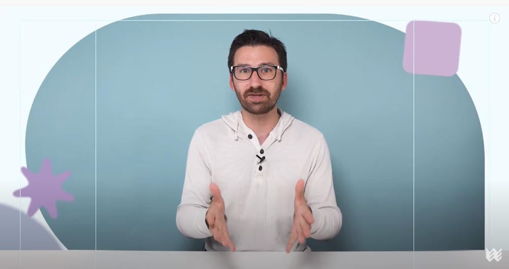 A bearded man in glasses wearing a white hooded shirt and standing in front of a blue background holds out his hands while talking to the camera. He is surrounded by two purple graphic shapes and is framed within a light, white frame.