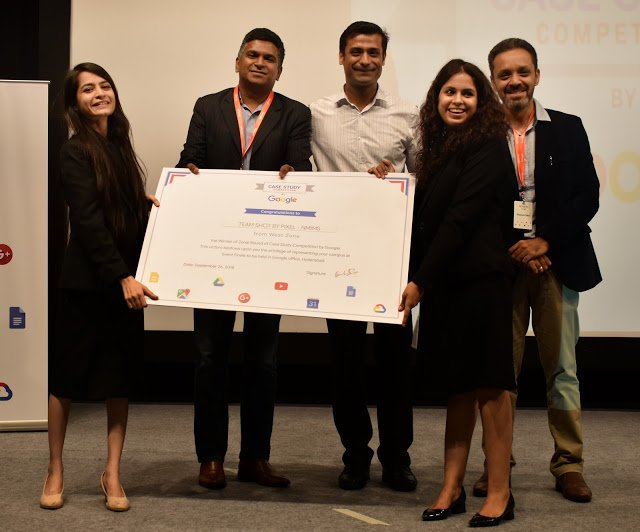 Snehal and four teammates holding large certificate indicating they won the case challenge.