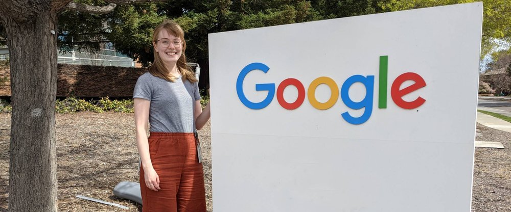 Woman standing next to a Google sign. On her left is a tree trunk, and behind her are trees, a building and a low brick wall.