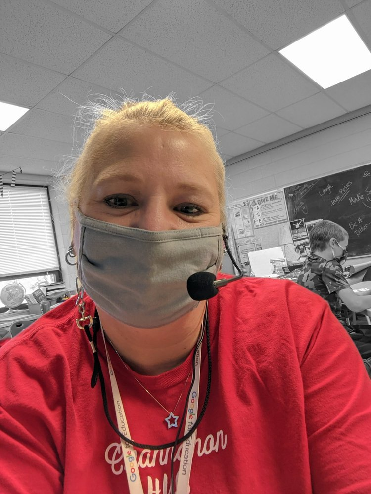 Renee sits at her desk with a mask teaching her students.