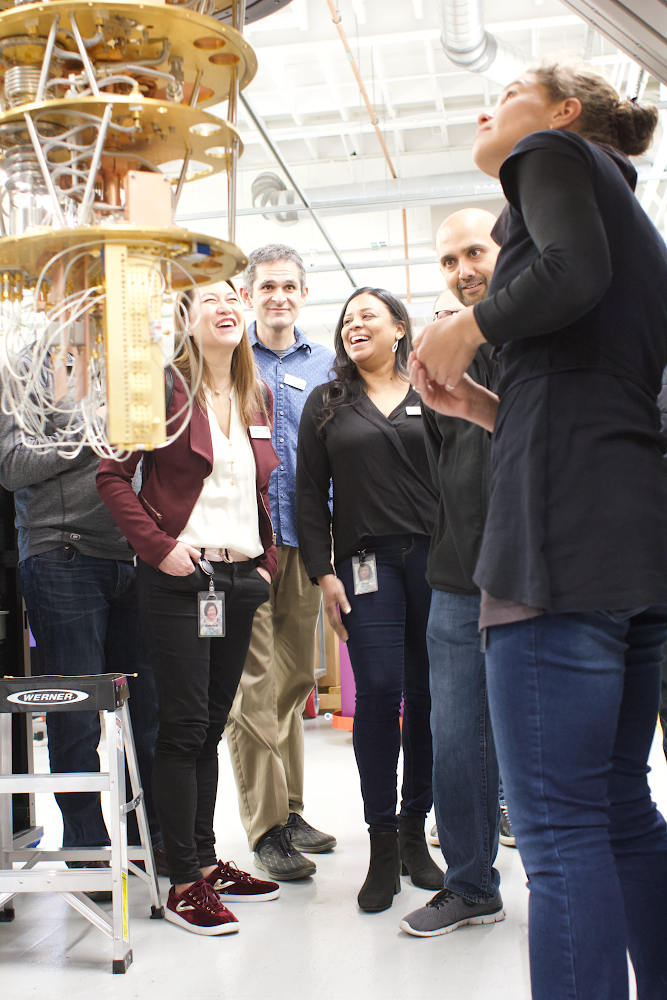 Researcher Marissa Giustina (right) in the Google AI Quantum hardware lab shares quantum computing hardware with Google executives. On the left, you can see the coldest part of a cryostat and some quantum hardware mounted to the bottom.