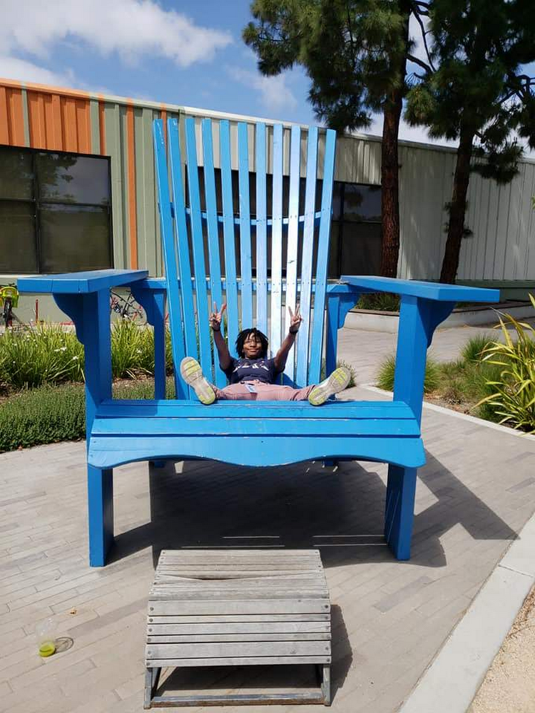 Patrice sitting in an oversized chair outdoors.