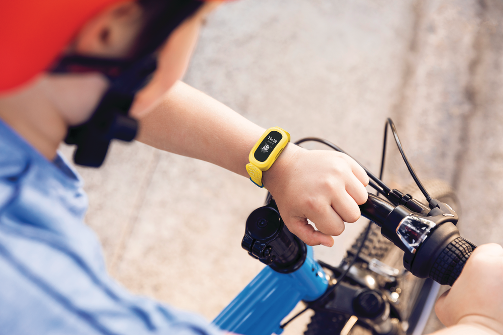 A person on a bike looks at their Ace 3 Special Edition: Minions device on their wrist