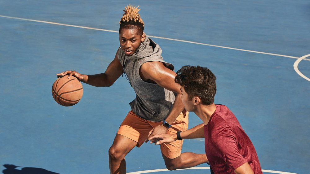 Two young men wearing athletic clothes playing basketball on a court wearing Fitbit Charge 5 trackers.