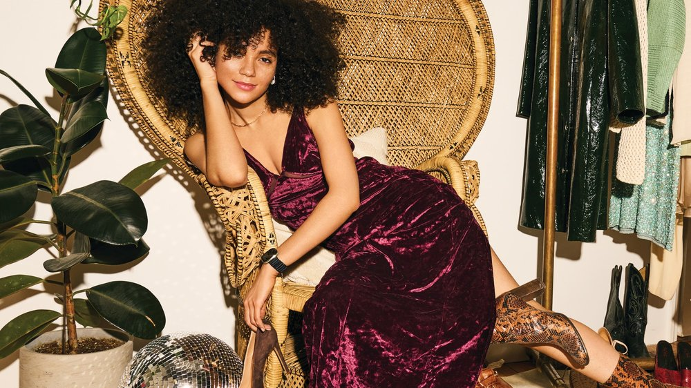 A young woman sitting in a chair wearing a v-neck maroon crushed velvet long dress and snakeskin boots models the new Fitbit + Brother Vellies band in black on her Fitbit smartwatch.