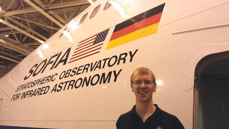 "Garrett standing in front of a modified Boeing 747SP airplane  with the words ""Sofia Stratospheric Observatory For Infrared Astronomy"" along with an American and German flag."