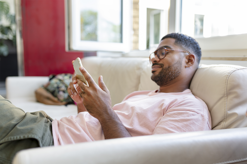 Man reclining on a couch and browsing his phone.