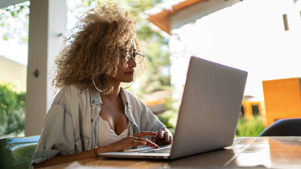 A woman wearing a denim shirt, glasses and hoop earrings sits at a table and uses a laptop.