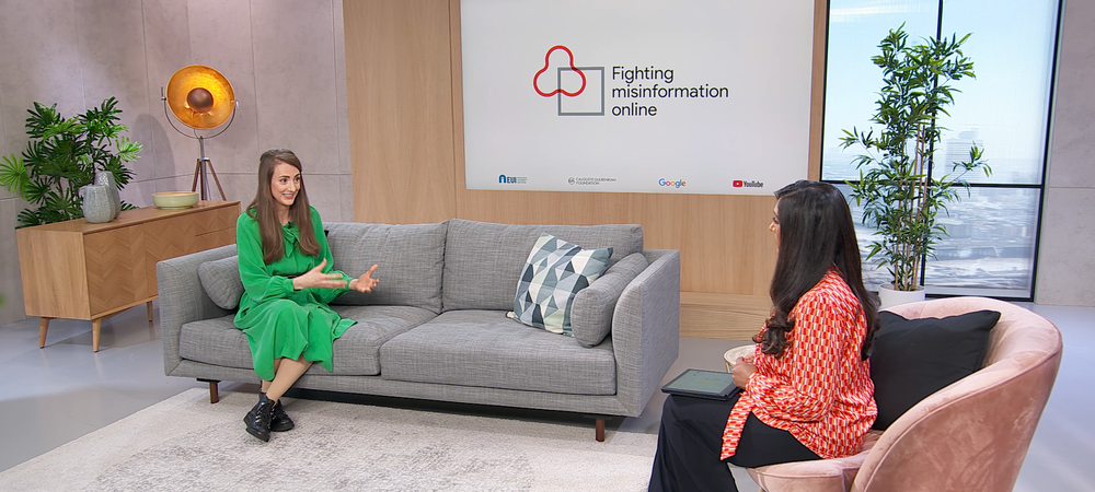 """In a studio setting, a woman on a sofa is speaking to a woman perpendicular to her on a chair, with a poster behind her saying """"Fighting misinformation online"""""""