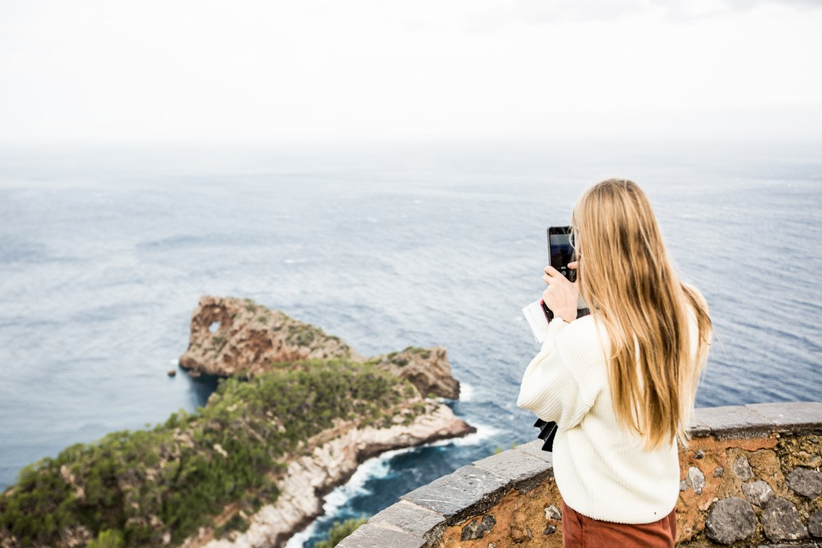 woman taking a photo of a coastal view