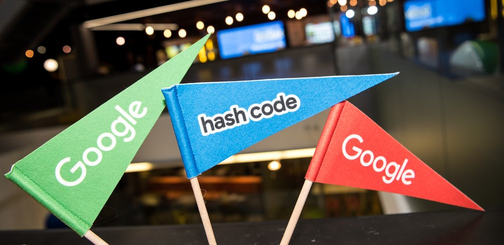 "Image showing three small flags, the first is green and says ""Google,"" the second is blue and says ""hash code"" and the third is red and says ""Google."""