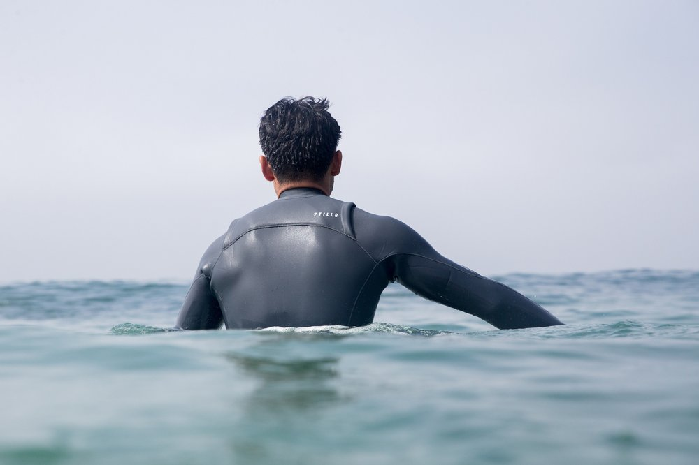 A surfer facing the horizon paddles out in a custom 7TILL8 wetsuit.