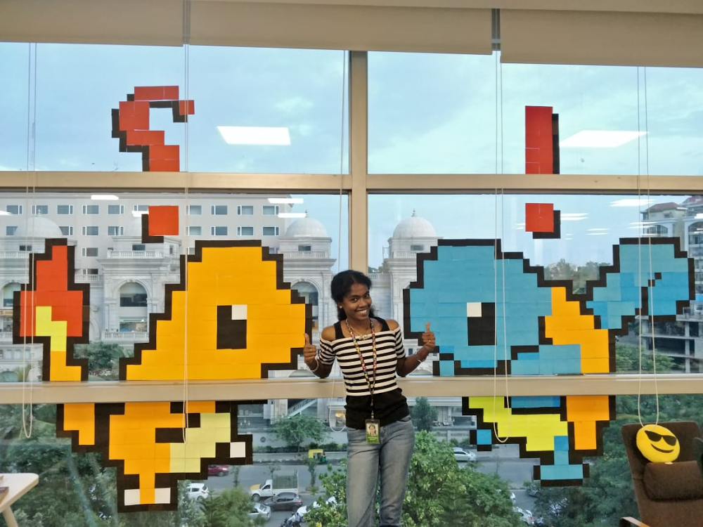 Kalaivani standing in front of a wall of post it art displaying the Pokemon, Charmander and Bulbasaur.