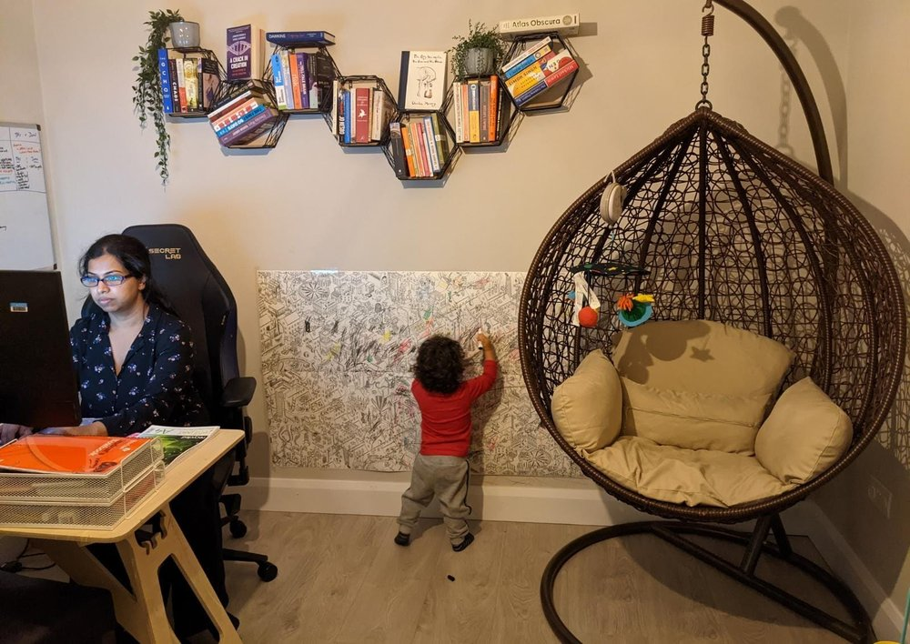 Krithika sitting at a desk working on a monitor. Behind her, her two year old child draws on paper stuck to the wall. Bookshelves and a swinging chair also decorate the room.