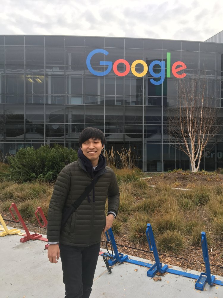 Inho stands in front of a building with the Google logo. In between are multicolored bike racks, some shrubs and a tree.