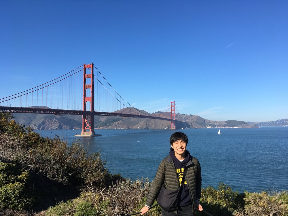 Inho posing with a smile in front of the Golden Gate Bridge. In the background is a red bridge stretching across a wide body of blue water, with sloping hills on the far side of the bridge. In the foreground are some green bushes.