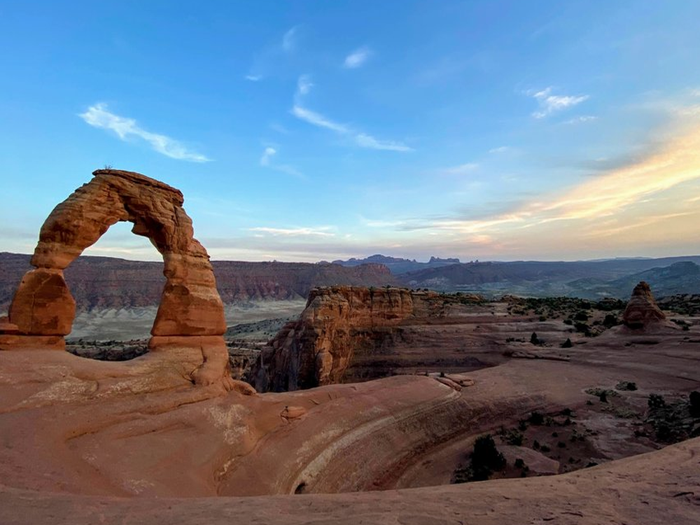 Delicate Arch rock formation at sunset.
