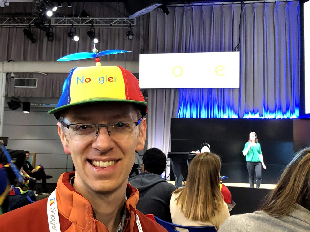 Garrett wearing a Noogler hat. In the background are other people sitting in chairs and a person standing on a stage holding the microphone.