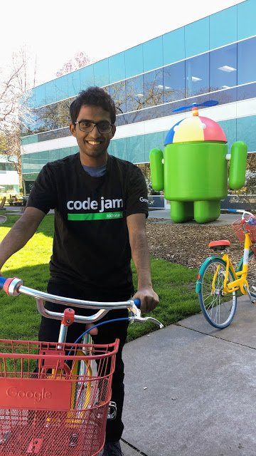 Satyaki on a bike in front of an Android statue. He is wearing a Code Jam shirt.