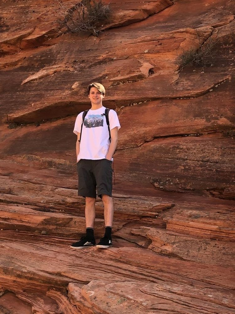 Aidan poses for a photograph while standing on a rocky structure.