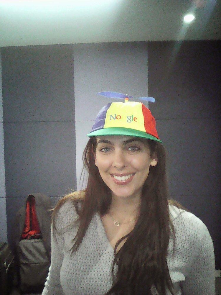 Dina in a Noogler hat indoors.