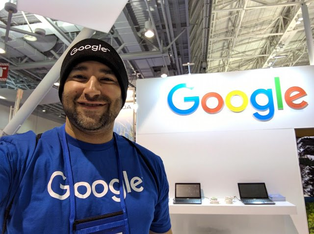 Jesus at a Google career fair booth wearing a google hat and beanie.