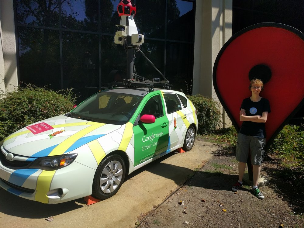 Frances standing in front of a large statue of the maps icon next to a street view car.