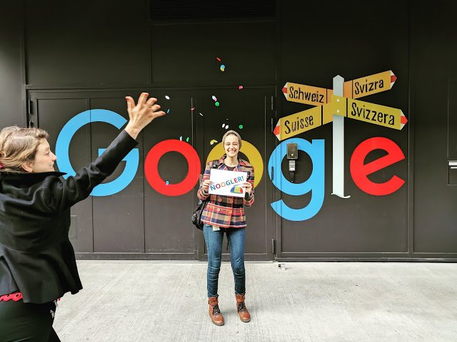 Nada in front of Google Zürich sign holding laptop with Noogler sticker as fellow Googler throws confetti int he air.