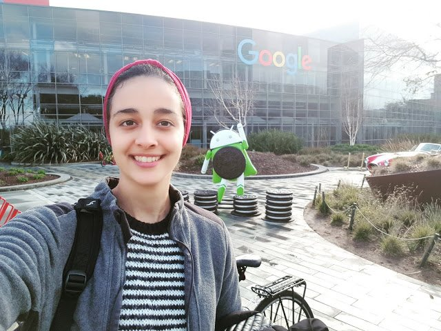 Selfie of Nada in front of Google sign and Android statue.