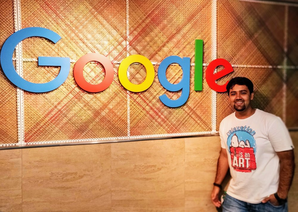 Nikhil standing indoors in front of a Google sign.