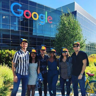Callen and other Nooglers in hats in front of Google headquarters sign.