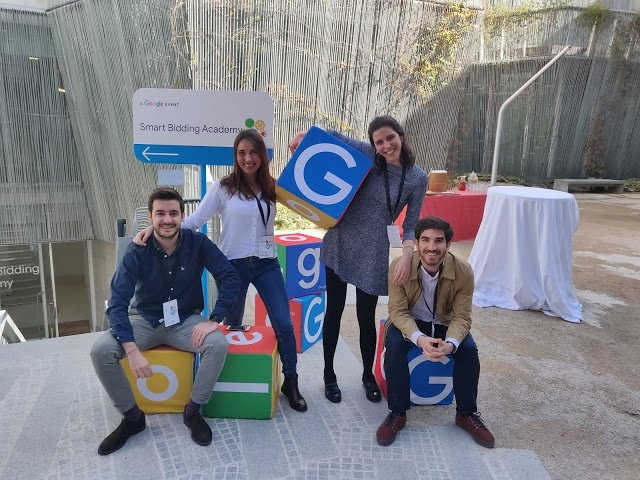 Four people sitting on and holding boxes painted with the Google letters and colors.