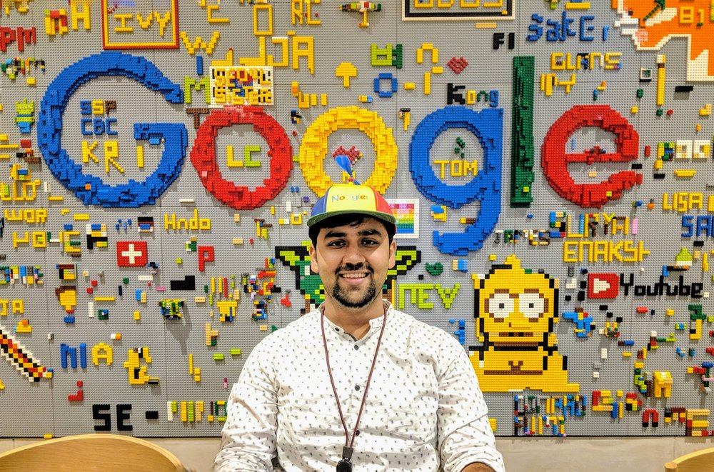 Nikhil wearing a Noogler hat sitting in front of a wall made of legos.