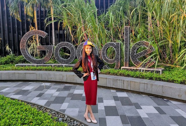 Snehal standing outdoors standing in front of large Google sign and foliage.