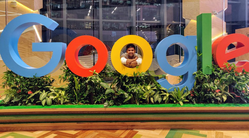 Nikhil standing indoors behind a large Google sign.