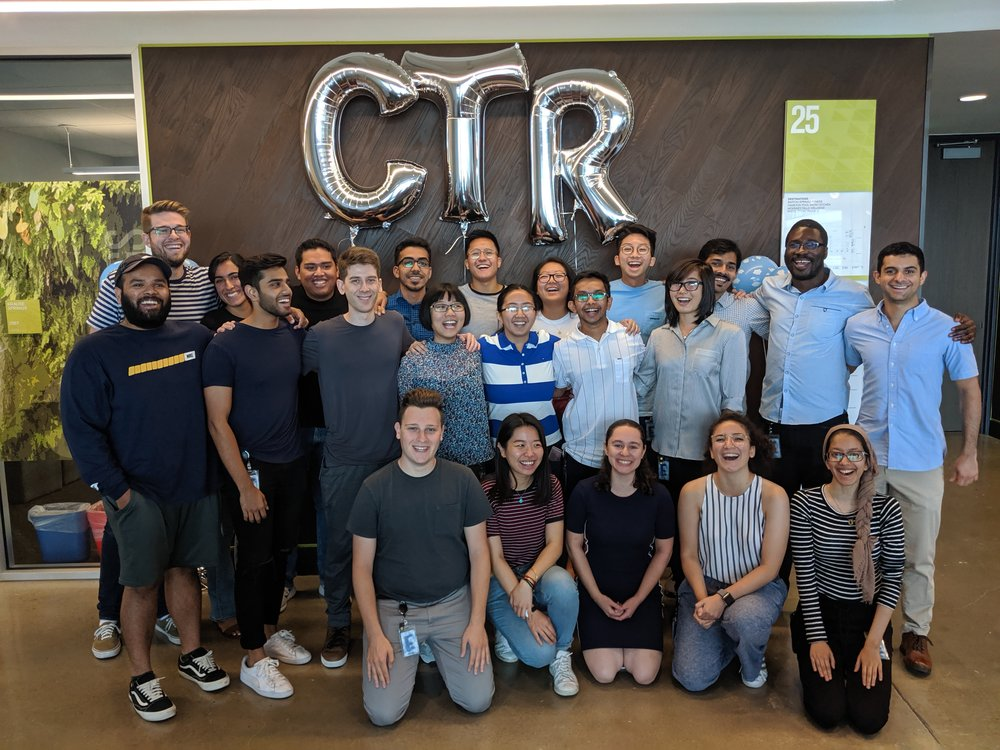"Group of individuals in front of large balloons letters reading ""CTR""."