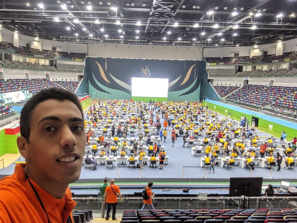 Yosri at the International Olympiad of Informatics 2019 in Baku, Azerbaijan. Yosri looks over an arena where participants in yellow and orange shirts sit at tables and work at laptops.
