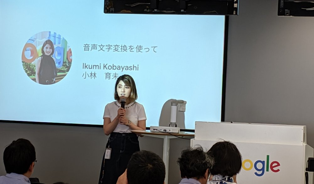 Ikumi speaking into a microphone in front of a large group. A slide is projected behind her introducing herself.